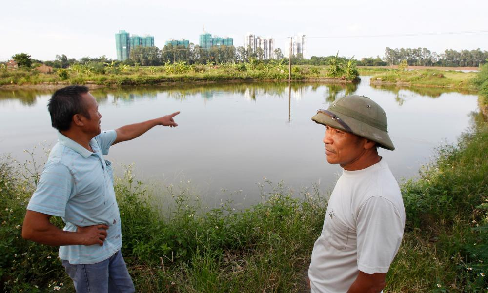 Dang Van Dat points to an Ecopark construction site as he stands with veteran Le Dung on an area involved in April 24's land seizure in Van Giang district<br />Dang Van Dat.