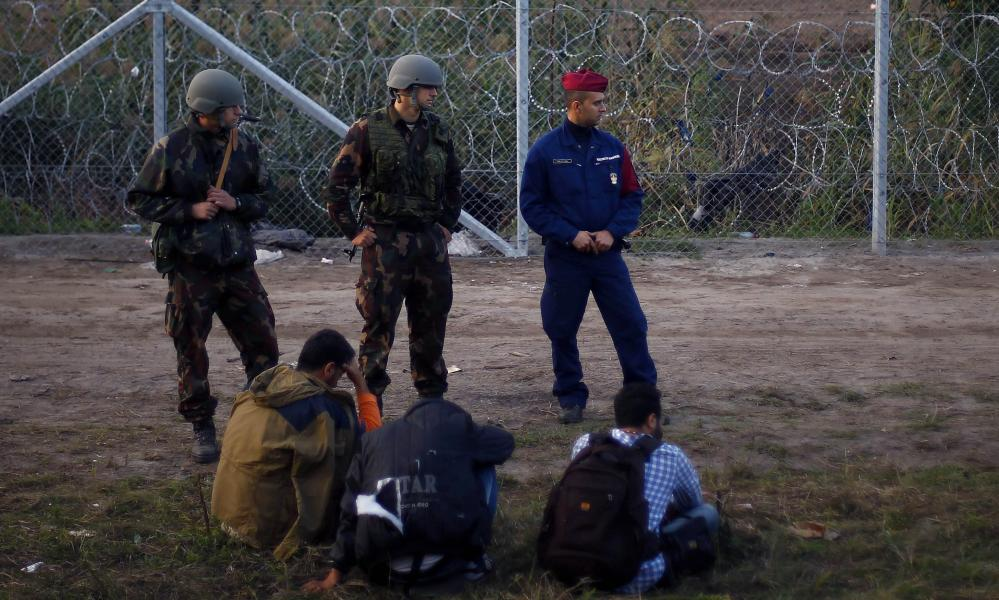 Migrants arrested by Hungarian police officers and soldiers after they tried to cross the border line between Serbia and Hungary in Roszke, southern Hungary, on Tuesday.