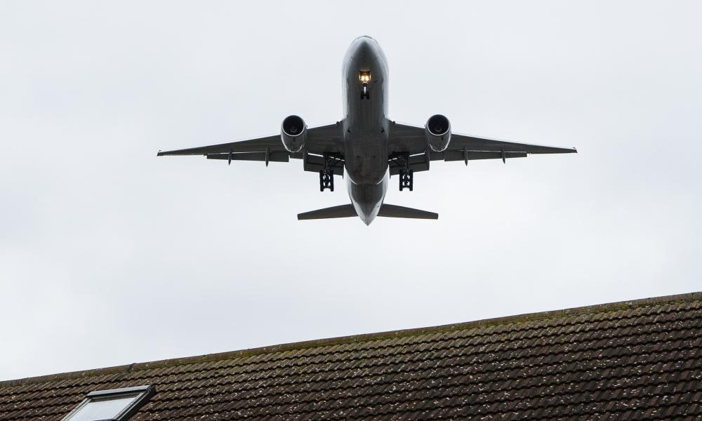 An aircraft flies over residential houses in Hounslow as it prepares to land at London Heathrow airport.