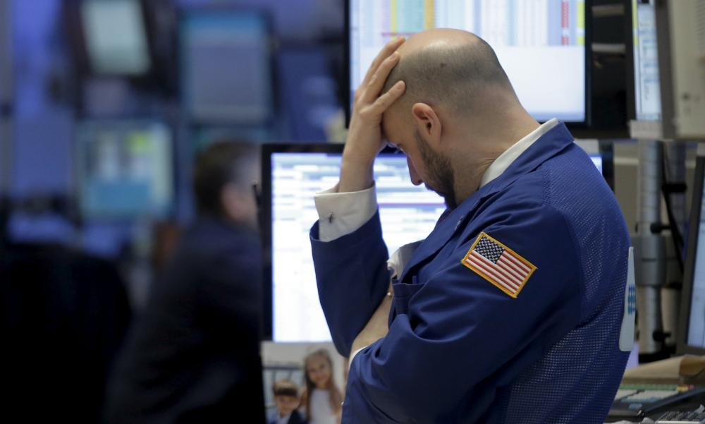 Traders at the New York Stock Exchange|: US confidence slips as markets slump.