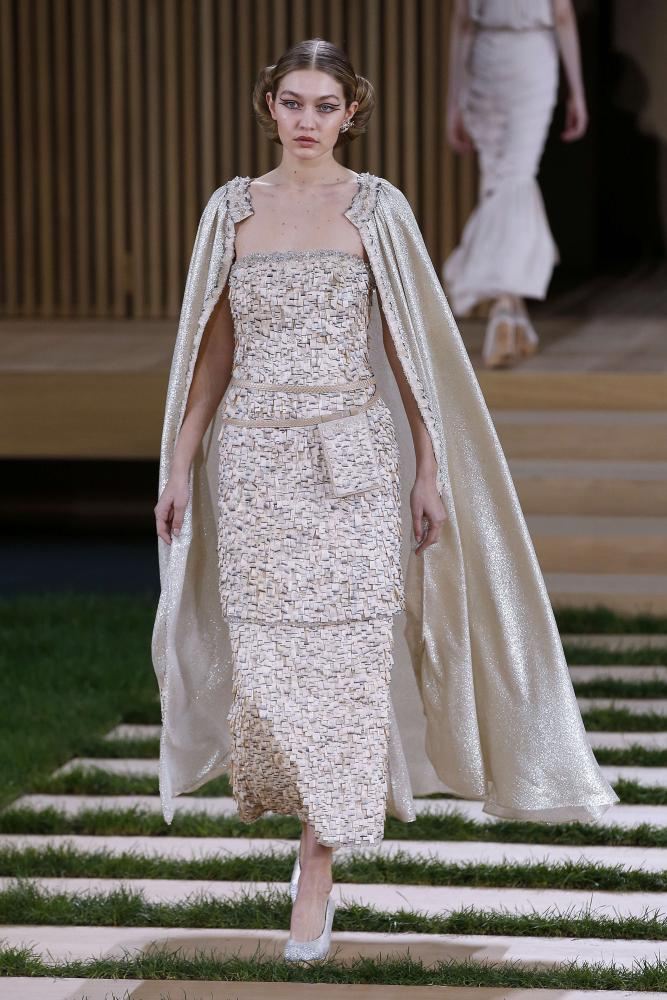 Gigi Hadid walks for Chanel in a cape.