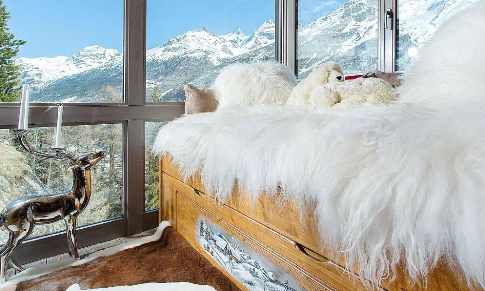 Bedroom with mountain views in Stirling Chalet in Saas Fe, Switzerland.