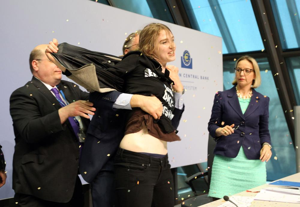 A woman interrupts a press conference by Mario Draghi, President of the European Central Bank (ECB) following a meeting of the Governing Council in Frankfurt / Main, Germany, on April 15, 2015. AFP PHOTO / DANIEL ROLANDDANIEL ROLAND/AFP/Getty Images