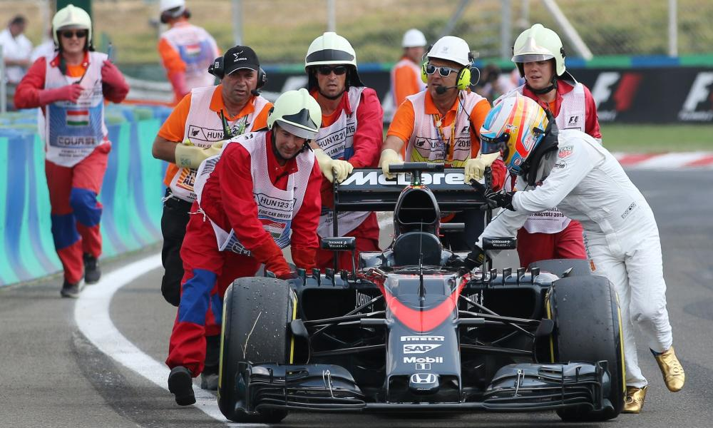 Track marshals help McLaren's Fernando Alonso push his car after it broke down during qualifying for the Hungarian Grand Prix