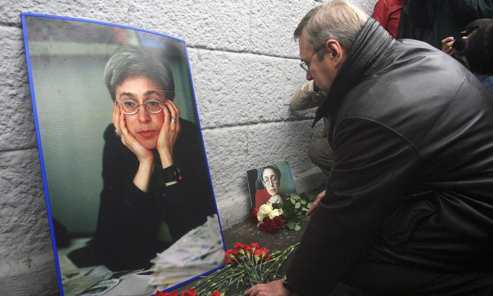 Former Russian prime minister Mikhail Kasyanov lays flowers at the house where journalist Anna Politkovskaya was killed in 2007.