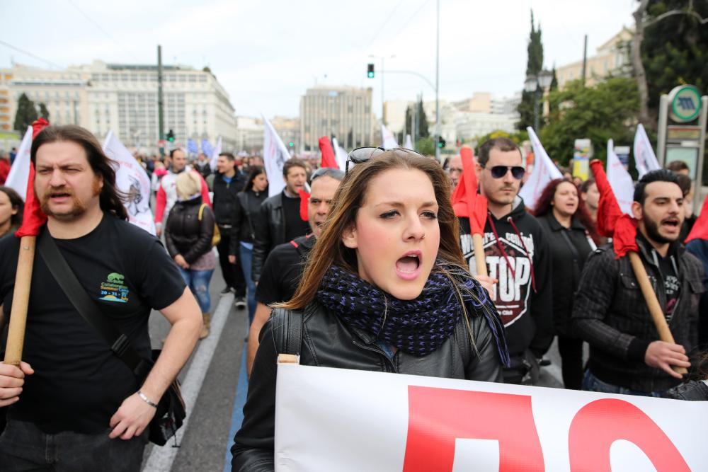 Members of the PAME Communist-affiliated shout slogans during a 24-hour nationwide general strike in Athens, Thursday, Feb. 4, 2016. Unions called the strike to protest pension reforms that are part of Greece's third international bailout. The left-led government is trying to overhaul the country's ailing pension system by increasing social security contributions to avoid pension cuts, but critics say the reforms will lead many to lose two-thirds of their income to contributions and taxes. (AP Photo/Petros Giannakouris)