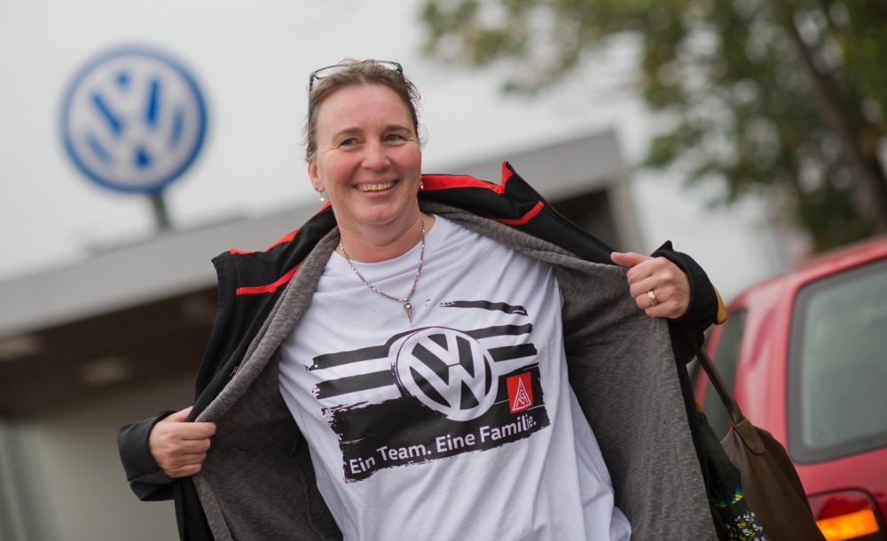 Volkswagen<br />06 Oct 2015, Wolfsburg, Germany --- VW employee Birgit Schuettke shows off an IG Metall shirt written with 'One Team. One Family.' at the end of the works assembly at Gate 17 at the Volkswagen factory in Wolfsburg, Germany, 06 October 2015. Photo: JULIAN STRATENSCHULTE/dpa --- Image by © Julian Stratenschulte/dpa/Corbis