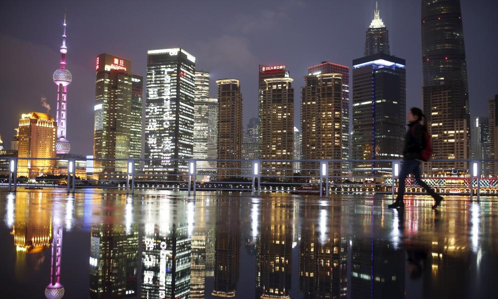 A woman walks at the Bund in front of the financial district of Pudong in Shanghai, in this March 5, 2015 file photo. China's economy grew 7.0 percent in the first quarter of 2015, as expected but still its slowest rate in six years, reinforcing bets that policymakers will take more steps to bolster growth. REUTERS/Aly Song/Files