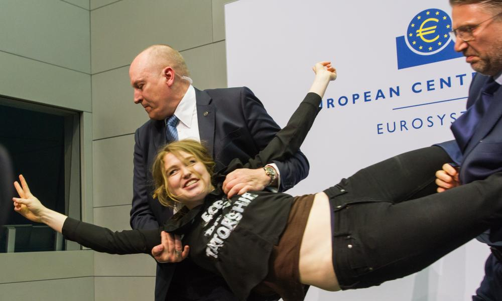 "A protester who jumped on top of ECB president Mario Draghi's desk during a news conference at the European Central Bank is detained by security. Her shirt reads ""End the ECB Dick-tatorship""."