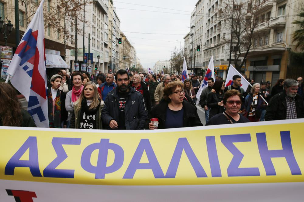 Members of the PAME Communist-affiliated hold a banner reads in Greek ''Social Security'' during a 24-hour nationwide general strike in Athens, Thursday, Feb. 4, 2016. Unions called the strike to protest pension reforms that are part of Greece's third international bailout. The left-led government is trying to overhaul the country's ailing pension system by increasing social security contributions to avoid pension cuts, but critics say the reforms will lead many to lose two-thirds of their income to contributions and taxes. (AP Photo/Petros Giannakouris)