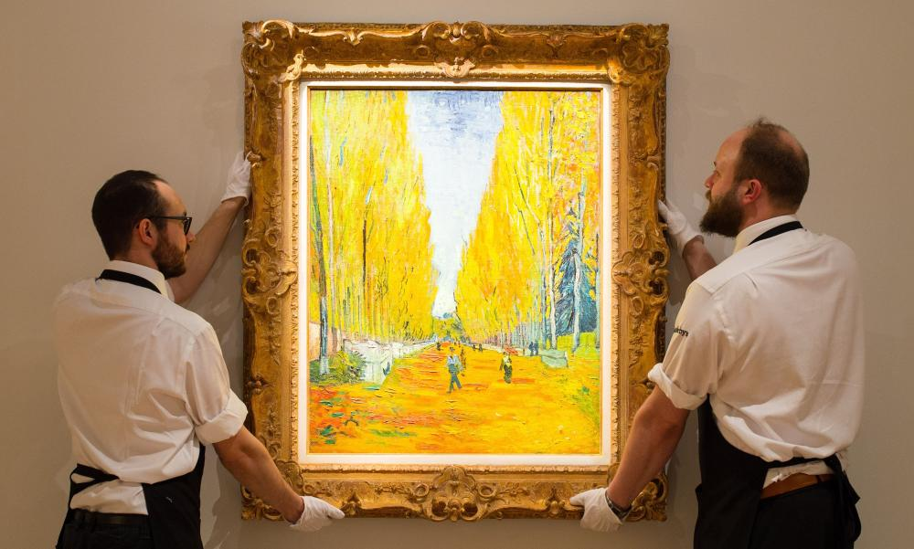 Gallery staff adjust L'Allee des Alyscamps by Vincent van Gogh at Sotheby's.