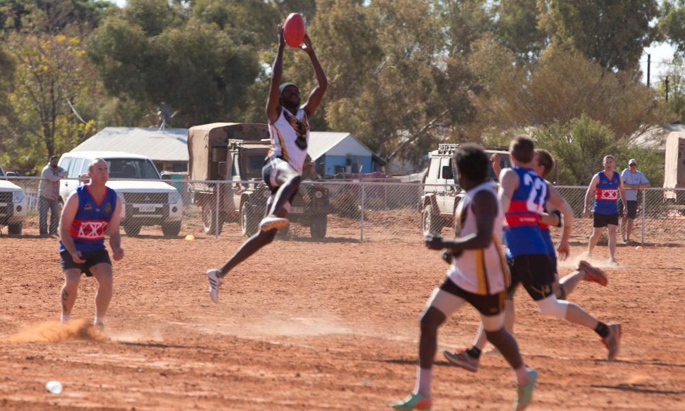A Titjikala Hawks player, Shaun Marshall, takes a mark during a friendly game against an army team. The Hawks won.