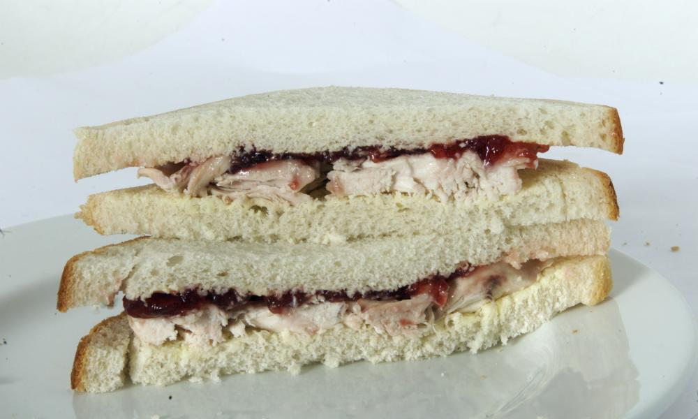 A turkey sandwich with cranberry sauce.