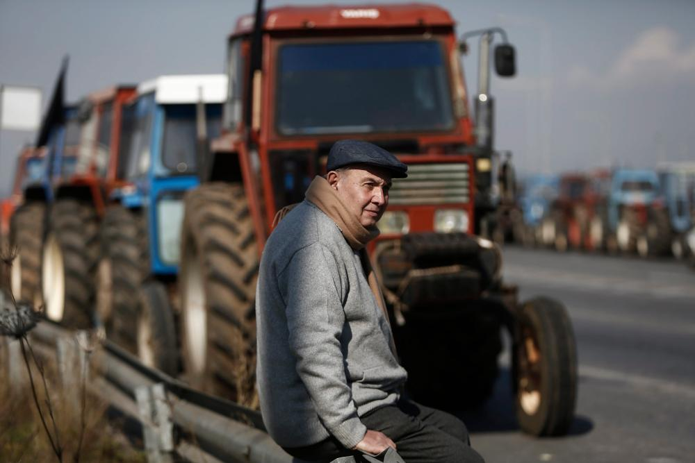 Farmers protest against the governmentÕs proposed tax and pension reforms near Athensepaselect epa05133482 A man sits in front of parked tractors blocking a point, on a road that leads to the international airport, during a protest in Koropi, near Athens, Greece 29 January 2016. Greek farmers protesting against the government's proposed tax and pension reforms announced they will block the Athens-Thessaloniki motorway Tempi Valley for six hours on Friday, following a decision by the Thessaly farmers' coordination committee. EPA/YANNIS KOLESIDIS