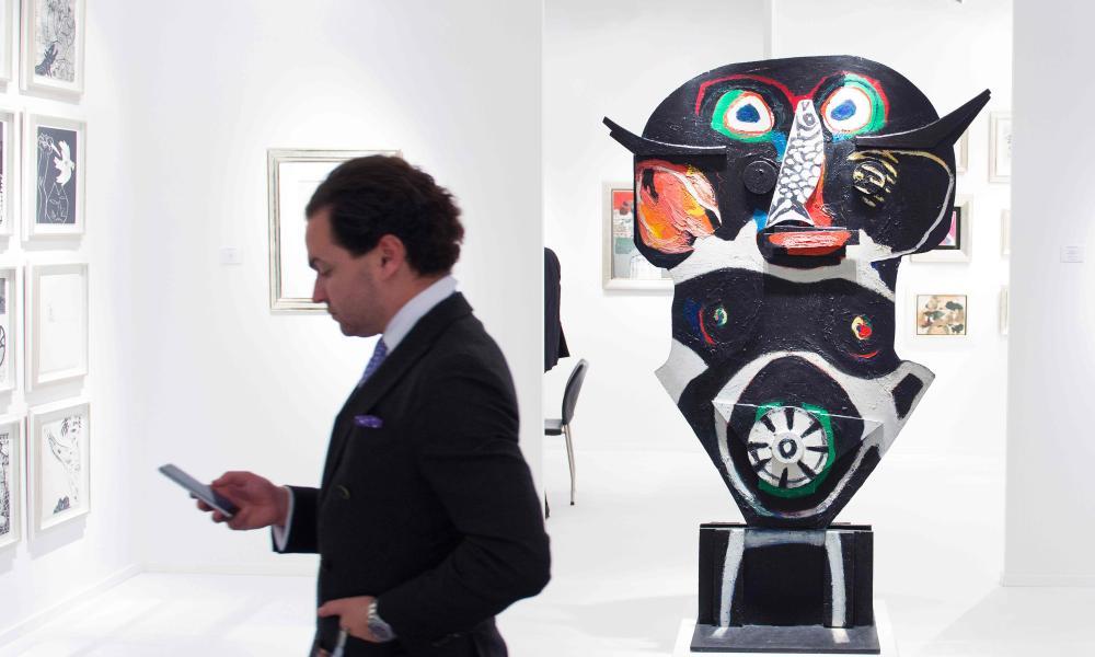 A man walks past La Vierge Noire by Dutch artist Karel Appel at the TEFAF art fair.