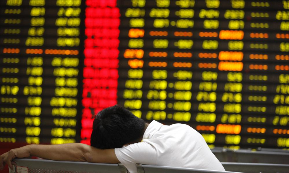An investor watches shares at a stock exchange in Huaibei, Anhui province, China, on 'Black Monday'