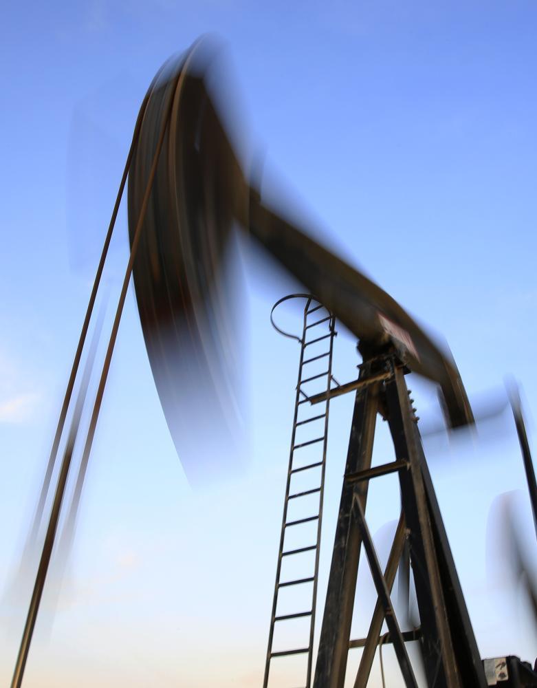 An oil pump works at sunset Monday, Dec.7, 2015, in the desert oil fields of Sakhir, Bahrain.