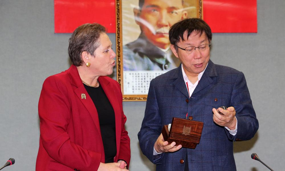 Taipei Mayor Ko Wen-je receives a gift of a watch from visiting British Transport Minister Baroness Susan Kramer during a meeting in Taipei.