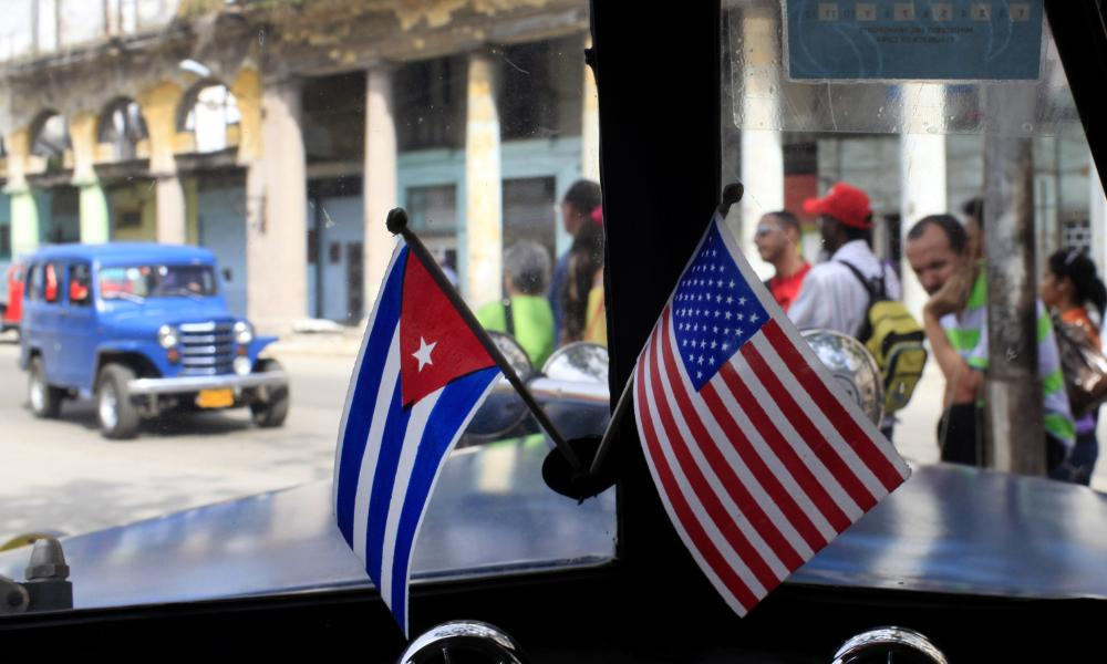 Miniature flags of Cuba and the United States are displayed on the dash of an American classic car in Havana, Cuba.