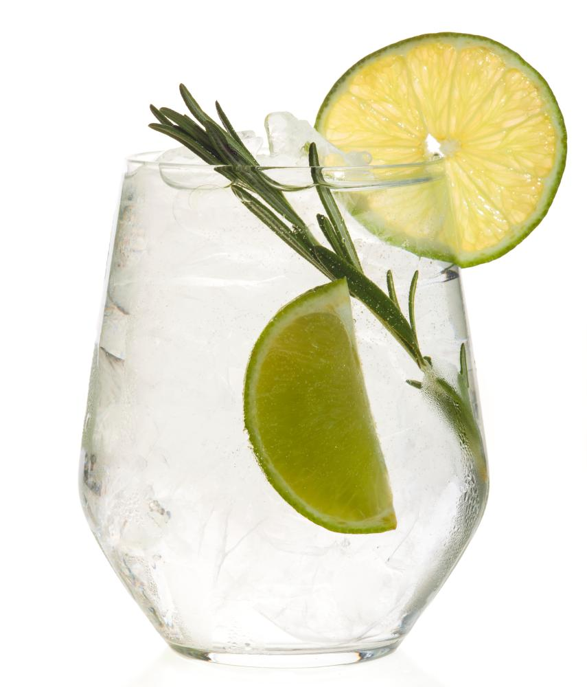 Glass with alcoholic drink with lime and ice isolated on white background.<br>EYX9EX Glass with alcoholic drink with lime and ice isolated on white background.