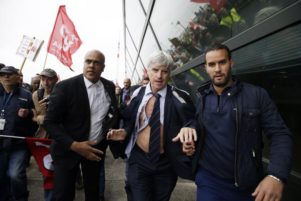 Director of Air France in Orly Pierre Plissonnier, nearly shirtless, runs away from the demonstrators, helped by security officers, after several hundred of employees invaded the offices of Air France, interrupting the meeting of the Central Committee (CCE) in Roissy-en-France, on October 5, 2015. Air France-KLM unveiled a revamped restructuring plan on October 5 that could lead to 2,900 job losses after pilots for the struggling airline refused to accept a proposal to work longer hours. AFP PHOTO / KENZO TRIBOUILLARDKENZO TRIBOUILLARD/AFP/Getty Images