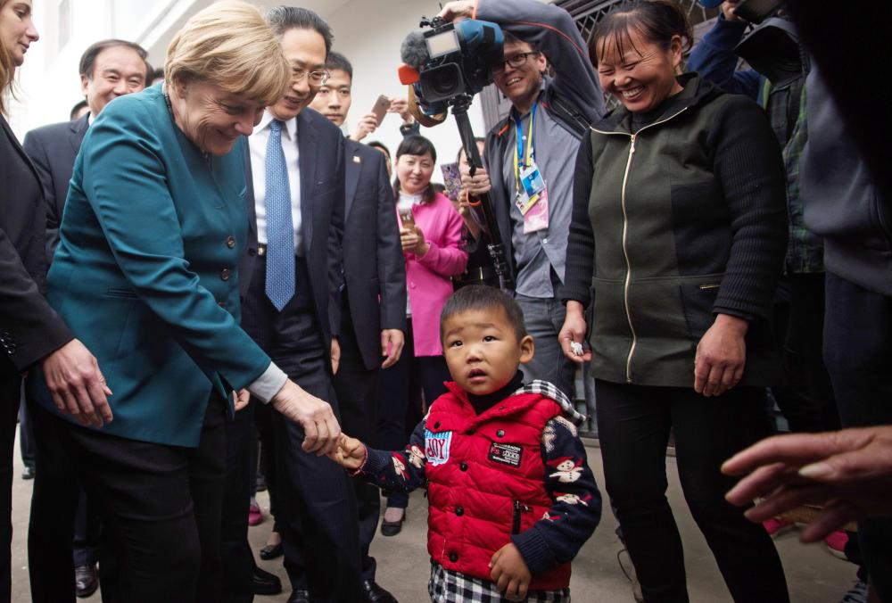 Angela Merkel<br />German Chancellor Angela Merkel , left, greets village children in Baohe district of Hefei, China, Friday, Oct. 30, 2015. (Johannes Eisele/Pool photo via AP)