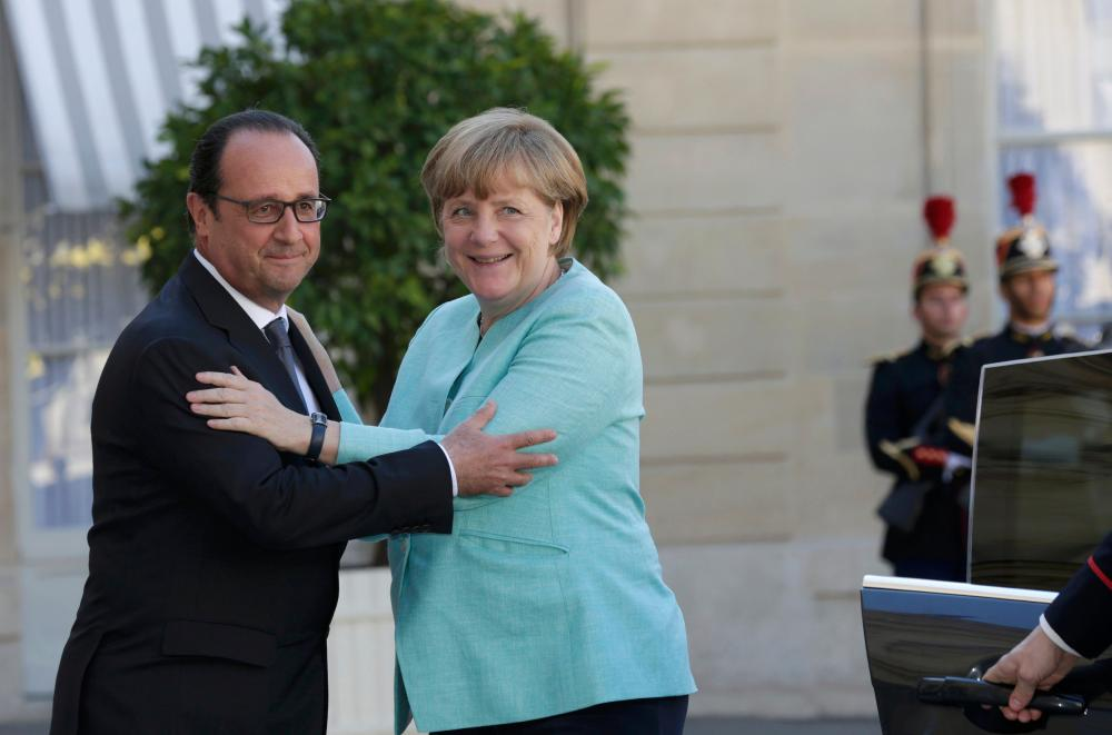 French President Francois Hollande welcomes German Chancellor Angela Merkel before talks and a dinner at the Elysee Palace in Paris