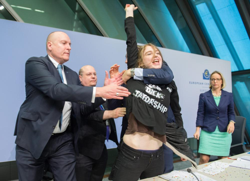 A female activist (C) wearing a t-shirt with a slogan reading: 'ECB Dick-Tatorship' is subdued by ECB security personnel after an incident at the press conference of the European Central Bank in Frankfurt, Germany, 15 April 2015.