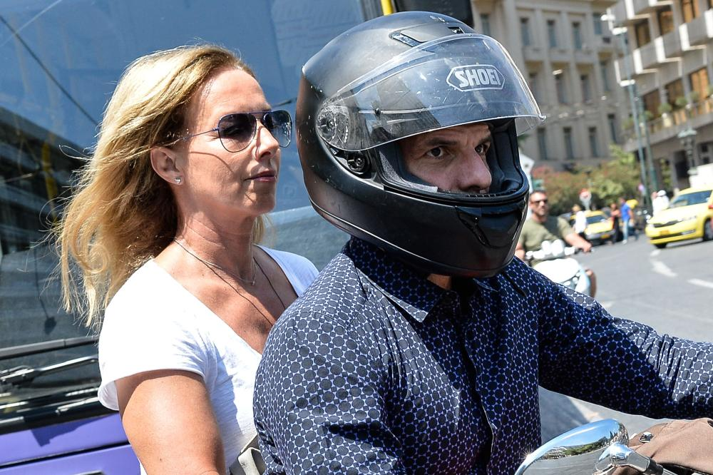 Greece's maverick finance minister Yanis Varoufakis, who announced his surprise resignation leaves the Ministry of Finance with his wife Danai on the back of a motorbike in downtown Athens, on July 6 2015.