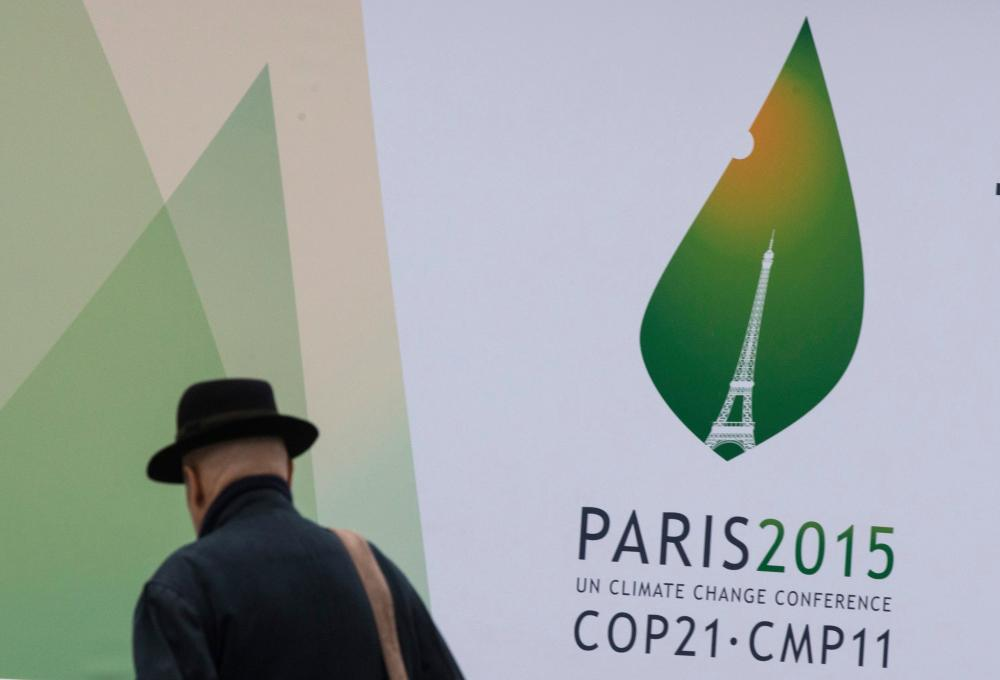A passerby walks in front of posters for the forthcoming COP 21 World Climate Summit in Paris, France, November 2, 2015. The upcoming conference of the 2015 United Nations Framework Convention on Climate Change (COP 21) will start in Paris on November 30, 2015. REUTERS/Philippe Wojazer