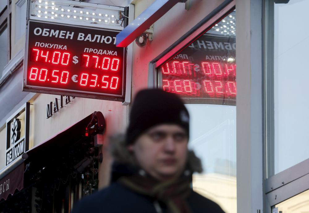 Man walks by board showing currency exchange rates of U.S. dollar and euro against rouble in central Moscow<br>A man walks by a board showing currency exchange rates of the U.S. dollar and euro against the rouble, in central Moscow, Russia, January 11, 2016. REUTERS/Maxim Zmeyev