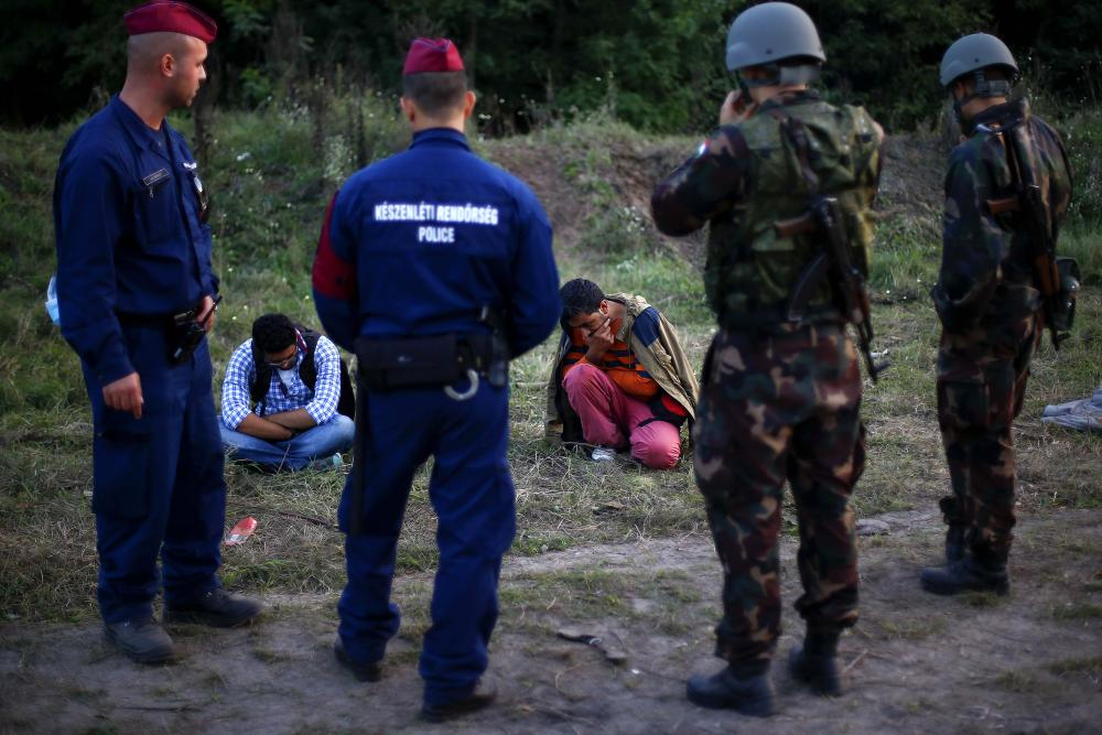 Migrants arrested by Hungarian police officers and soldiers after they tried to cross the border line between Serbia and Hungary in Roszke, southern Hungary.