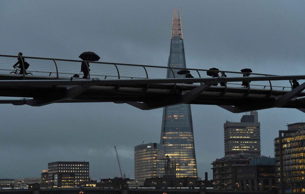 City workers crossing the Millennium footbridge at dawn.
