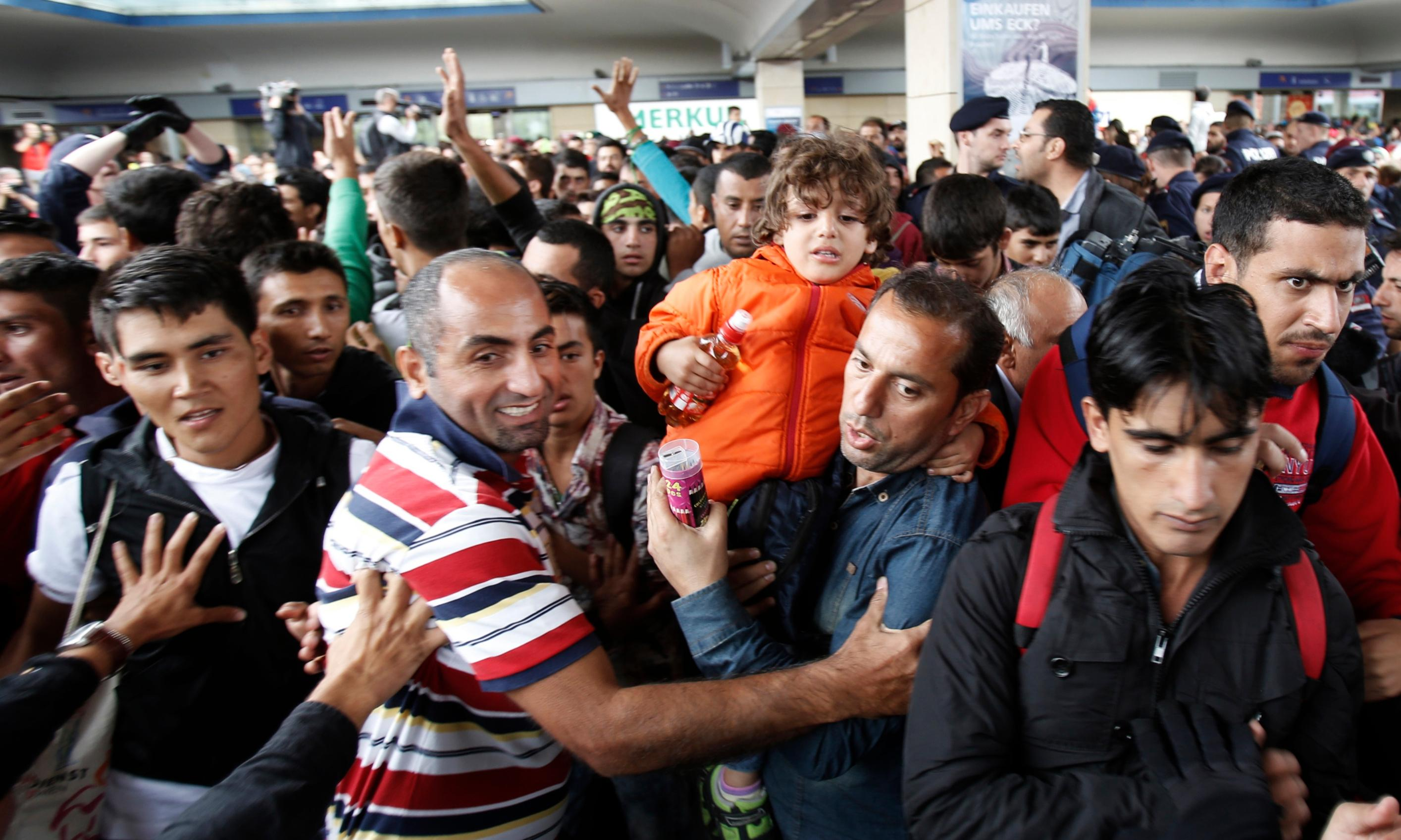 Elation as migrants are received with open arms in Austria and Germany