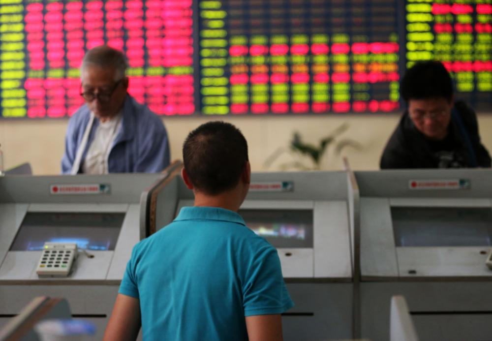 16 Oct 2015, Nanjing, Jiangsu Province, China --- Chinese investors look at prices of shares (red for price rising and green for price falling) at a stock brokerage house in Nantong city, east China's Jiangsu province, 16 October 2015.