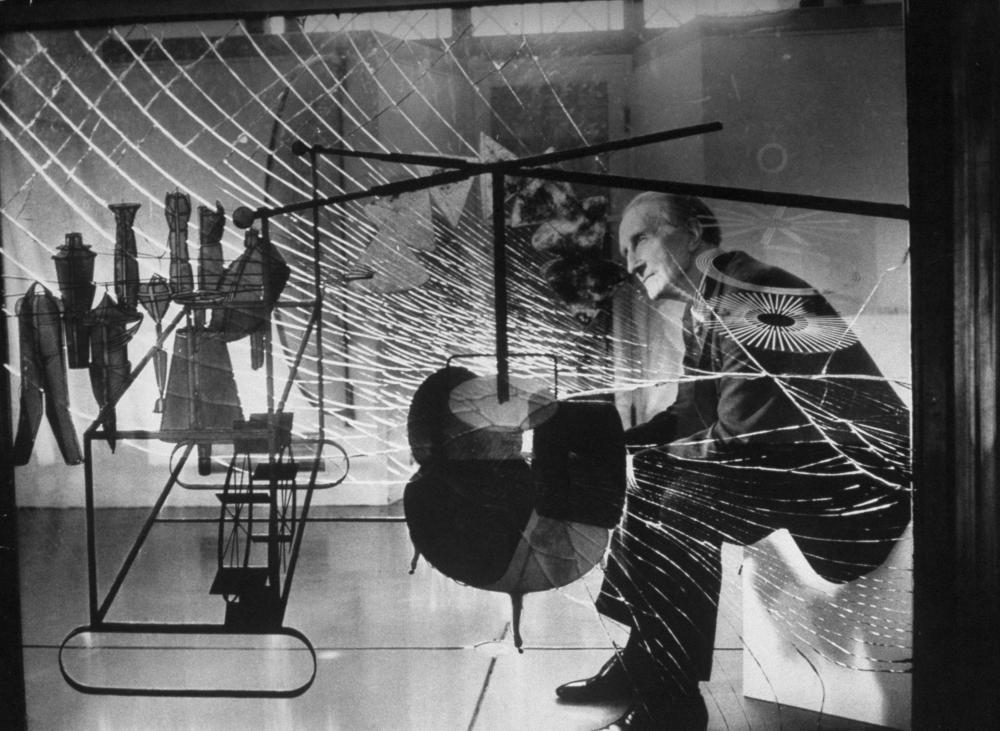 Marcel Duchamp being viewed through glass of his major work The Bride Stripped Bare by Her Bachelors.