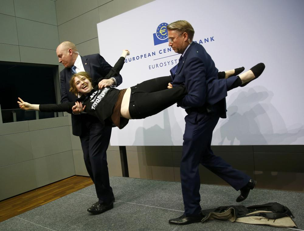 Security officers detain a protester who jumped on the table in front of the European Central Bank President Mario Draghi during a news conference in Frankfurt, April 15, 2015. The news conference was disrupted on Wednesday when a woman in a black T-shirt jumped on the podium. REUTERS/Kai Pfaffenbach