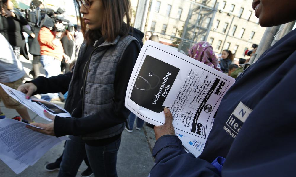 A New York City Health department official hands out information on the Ebola virus outside a school in the Bronx, New York .