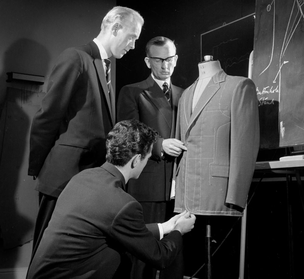 Three men training as tailors looking at the inside of a suit jacket