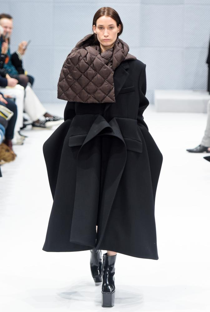 Model on catwalk in black coat