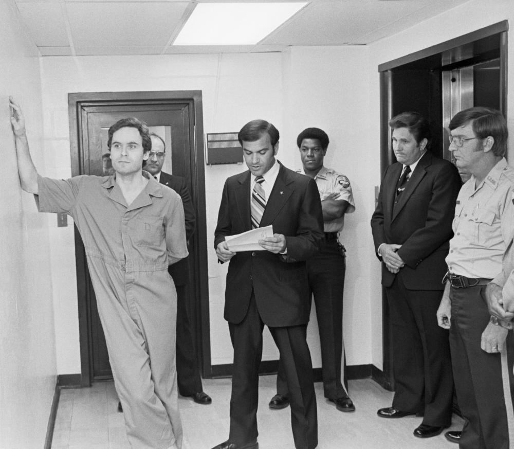 Ted Bundy (l) leans on the Leon County jail wall as an indictment charging him with the murders of two women is read to him.