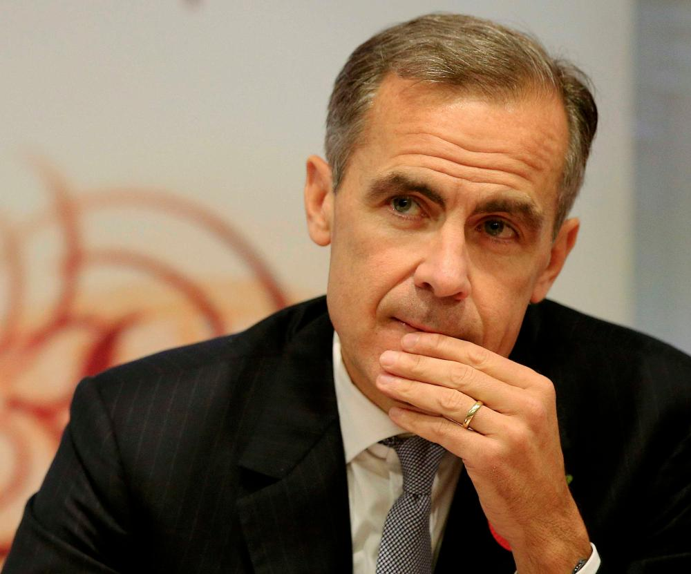 Bank of England Governor Mark Carney listens during an inflation report news conference at the Bank of England in London, Britain November 5, 2015. The Bank of England gave no sign that it was in any more of a hurry to raise interest rates on Thursday, predicting near-zero inflation would pick up only slowly even if borrowing costs stay on hold all of next year. REUTERS/Jonathan Brady/pool