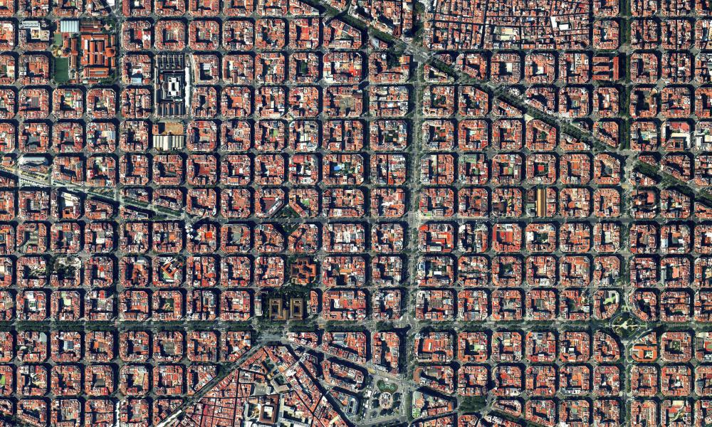 The Eixample district is characterised by its strict grid pattern, octagonal intersections, and apartments with communal courtyards.