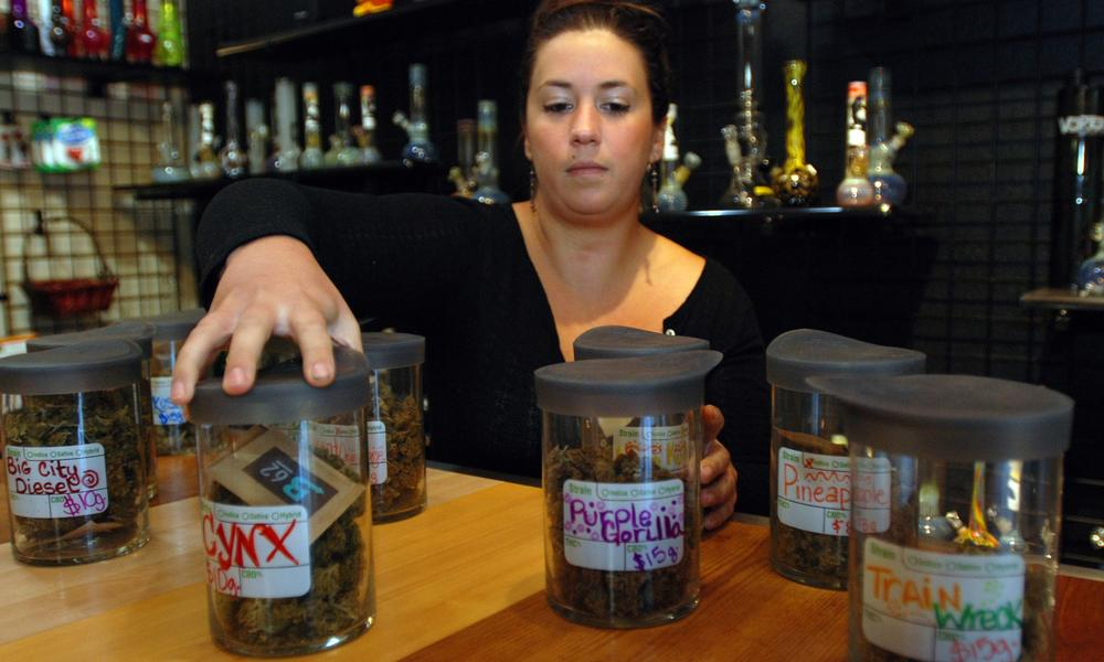Danielle Baldwin arranges canisters of medical marijuana at Puffs Smoke Shop in Ashland, Oregon.