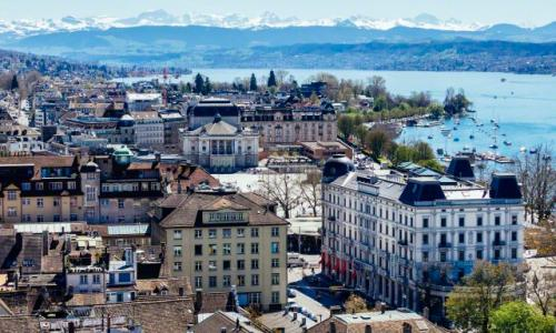 Zurich city view with mountains in the background on a clear, sunny day.
