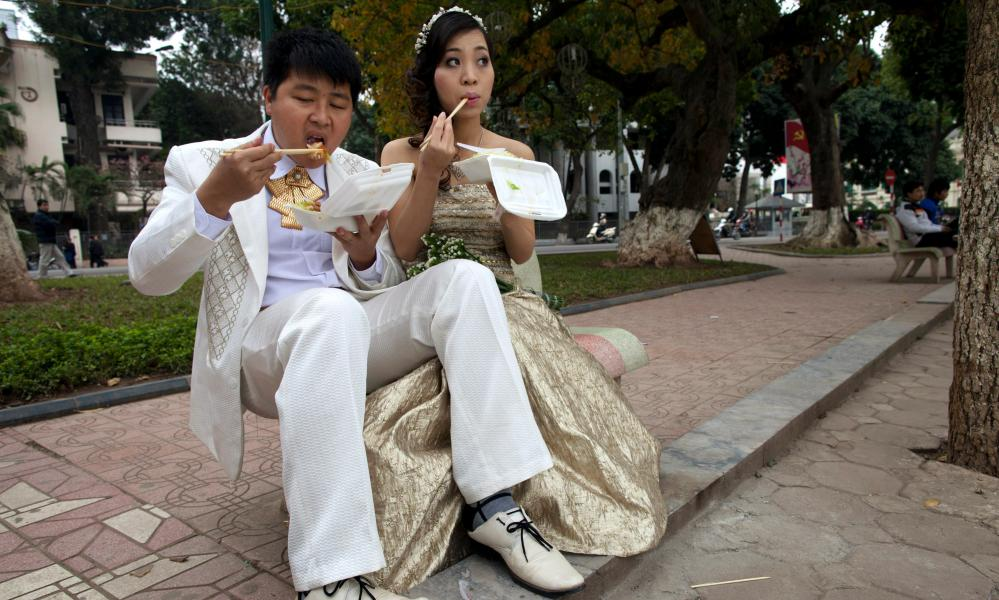 Wealthy newlyweds pose for a photographer in Hanoi.