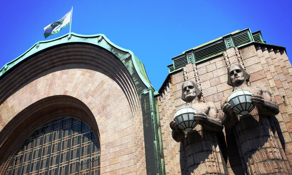 Statues holding spherical lamps at the entrance to Helsinki railway station, Finland