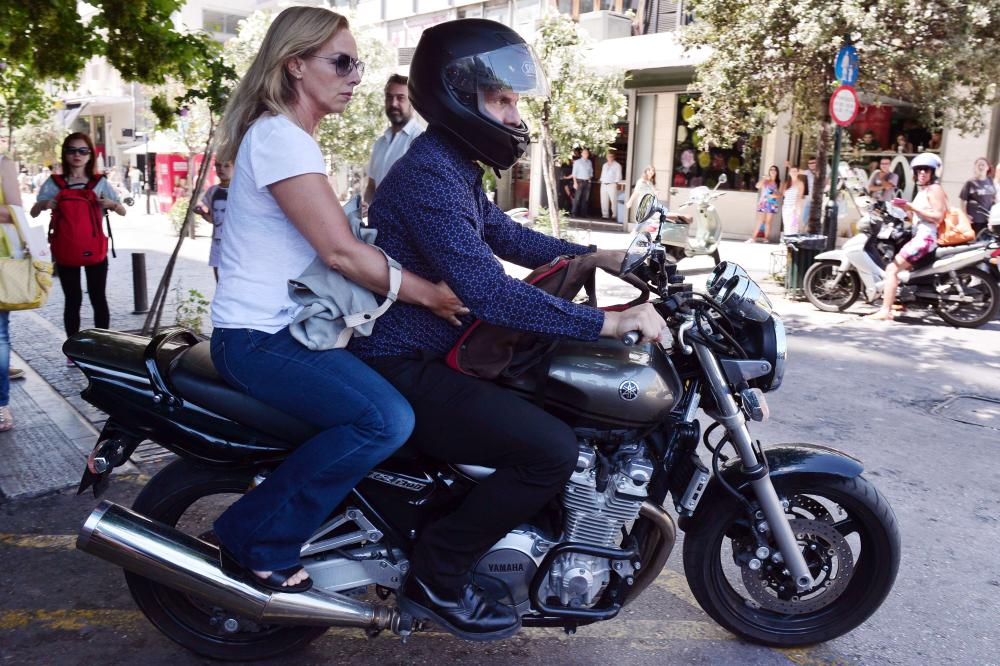 Outgoing Greek Finance minister Yanis Varoufakis leaves onto his motorcycle with his wife Danai after his resignation at the ministry of Finance in downtown Athens on July 6 2015. Varoufakis resigned in what appeared to be a concession by Prime Minister Alexis Tsipras to international creditors after his resounding victory in a historic bailout referendum. AFP PHOTO / LOUISA GOULIAMAKILOUISA GOULIAMAKI/AFP/Getty Images