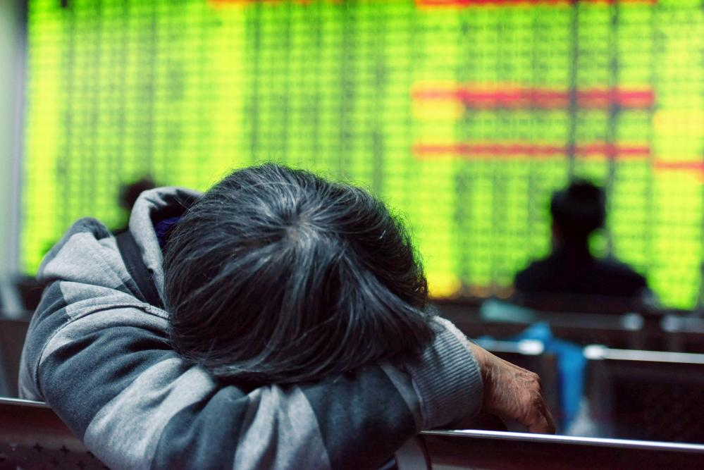 An investor rests in front of a screens showing stock market movements at a securities firm in Hangzhou, in eastern China's Zhejiang province on January 11, 2016. China's benchmark Shanghai stock index closed down 5.33 percent on January 11, as investors continued to worry over the state of the world's second largest economy, dealers said. AFP PHOTO CHINA OUTSTR/AFP/Getty Images
