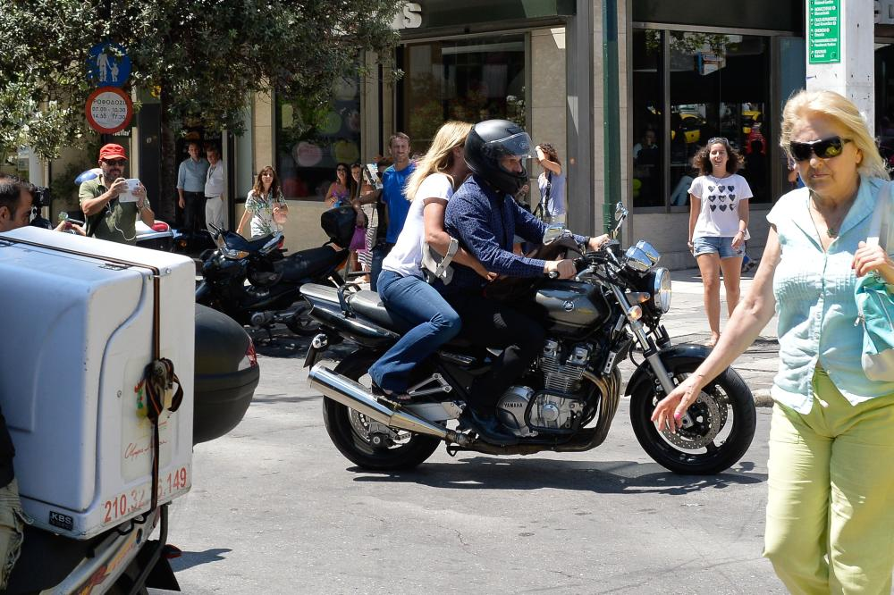 Greece's maverick finance minister Yanis Varoufakis, who announced his surprise resignation leaves the Ministry of Finance with his wife Danai on the back of a motorbike in downtown Athens, on July 6 2015. Germany dismissed Greece's bid to clinch a quick new debt deal after the country delivered a resounding 'No' to more austerity, appearing little moved by the surprise resignation of the Greek finance minister. AFP PHOTO / ANDREAS SOLAROANDREAS SOLARO/AFP/Getty Images
